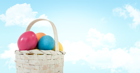 Digital composite of Easter eggs in basket in front of blue sky