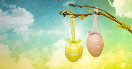 uncomfortable: Digital composite of Easter eggs on branch in front of cloudy sky