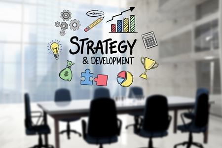 Digital composite of Strategy and development text surrounded by icons in office Stock Photo