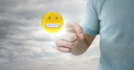 Digital composite of Man in tshirt pointing at emoji with flare against cloudy sky