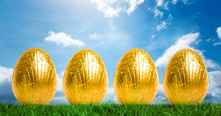 Digital composite of Gold Easter Eggs in front of blue sky