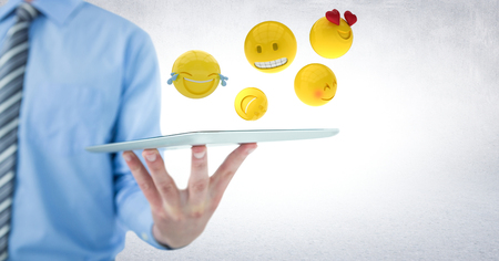 scrolling: Digital composite of Business man mid section holding tablet with one hand and emojis against white wall Stock Photo