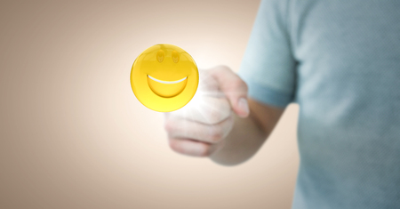 anthropomorphic: Digital composite of Man in tshirt pointing at emoji with flare against cream background Stock Photo