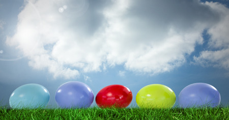 grass blades: Digital composite of Easter eggs in front of blue sky