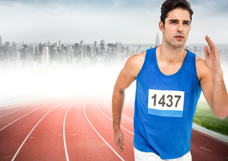 Digital composite of Male runner sprinting on track against blurry skyline Stock Photo