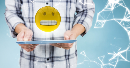 Digital composite of Man mid section with tablet, emoji, flare and network against blue background Stock Photo