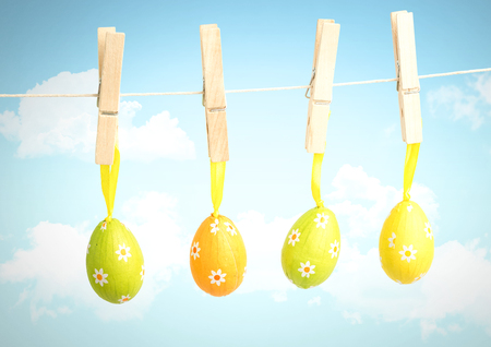 stack of files: Digital composite of Easter Eggs on pegs in front of blue sky