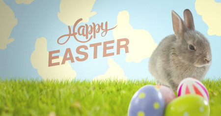 horizon over land: Digital composite of Happy Easter text with Easter rabbit with eggs in front of pattern Stock Photo