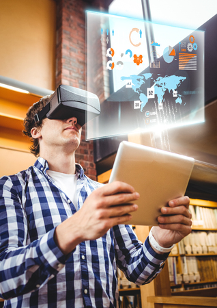 Digital composite of Man wearing VR Virtual Reality Headset with Interface and tablet Stock Photo