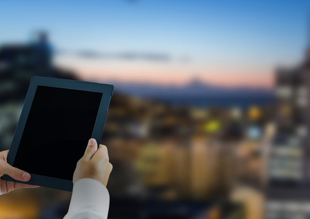 nigth: Digital composite of Hands with tablet in the city at nigth