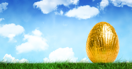Digital composite of Gold Easter egg in front of blue sky Stock Photo