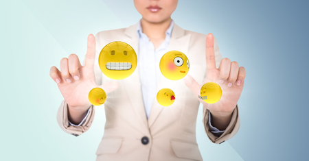 Digital composite of Business woman with emojis and flares between hands against blue background Stock Photo