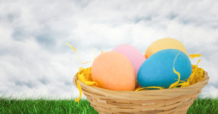 Digital composite of Easter eggs in front of cloudy sky