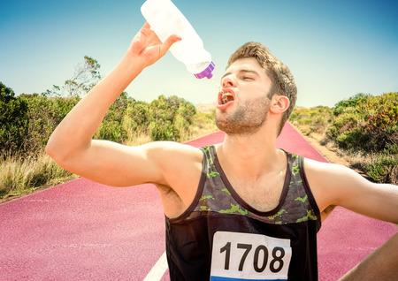 Digital composite of Male runner drinking on track in desert