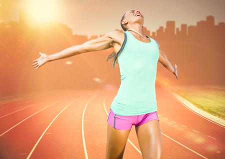 Digital composite of Female runner on track against orange flare and skyline