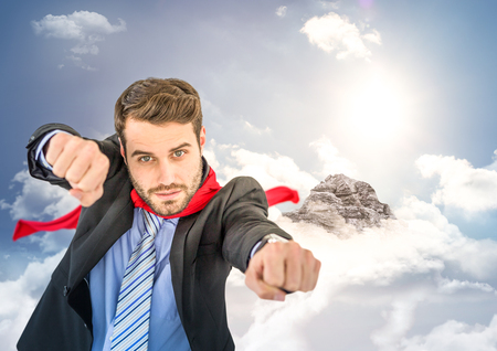 Digital composite of Business man superhero with hands out against mountain peak with clouds Stock Photo