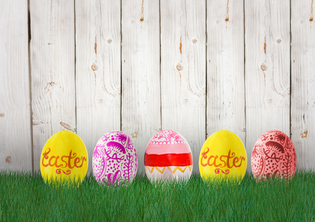 Digital composite of Easter yellow, orange and pink eggs in the garden Stock Photo