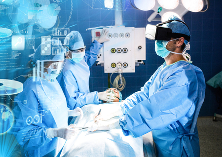 Digital composite of Doctors operating wearing VR Virtual Reality Headset with Interface Foto de archivo