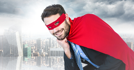 Digital composite of Business man superhero with head on hand against blurry skyline