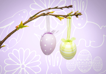 Digital composite of Easter eggs hanging on branch in front of pattern Stock Photo