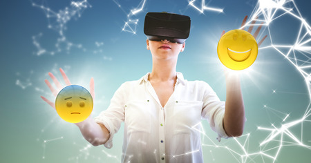 thoughtful: Digital composite of Woman in VR with network and emojis with flares against blue green background