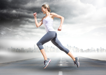 Digital composite of Female runner going across road with skyline and storm
