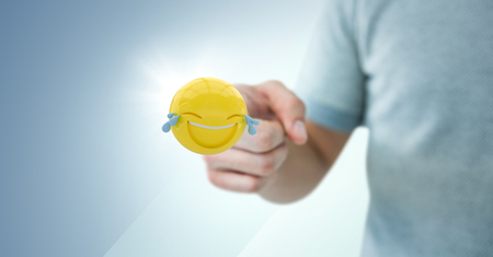 Digital composite of Man in tshirt pointing at emoji with flare against blue background