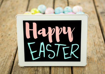 Digital composite of Pink and blue type on tablet on wood table with easter eggs
