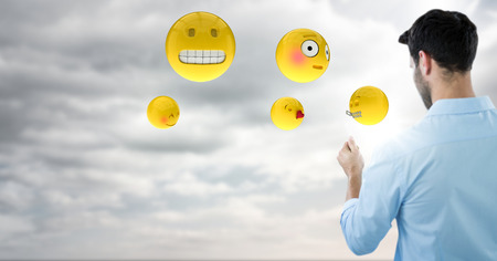 anthropomorphic: Digital composite of Back of man with emojis and flare against sky with clouds Stock Photo