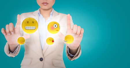 anthropomorphic: Digital composite of Business woman with emojis and flares between hands against blue background Stock Photo