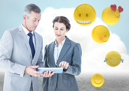 scrolling: Digital composite of Business people with tablet against cloud and ground with emojis