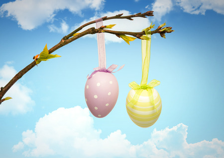 Digital composite of Easter eggs hanging on branch in front of blue sky