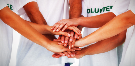 selfless: Group of volunteers putting hands together on white background
