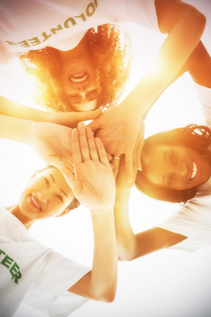 Directly below shot of volunteers stacking hands while standing against white background Stock Photo