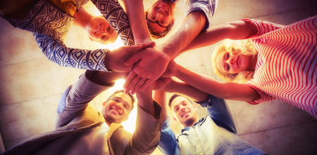 Low angle portrait of happy business team joining hands in office