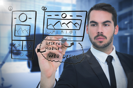 Focused businessman writing with marker against digitally generated image of workplace