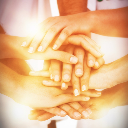 altruismo: Sección media de voluntarios juntando las manos sobre fondo blanco