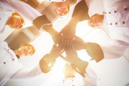 hotel staff: Chefs joining hands in a circle wearing uniforms in a kitchen
