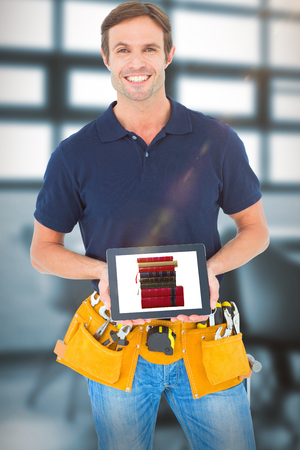Happy carpenter holding digital tablet against chairs arranged by table