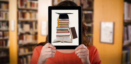 Woman holding digital tablet in front of her face against close up of a bookshelf Stock Photo - 75825358
