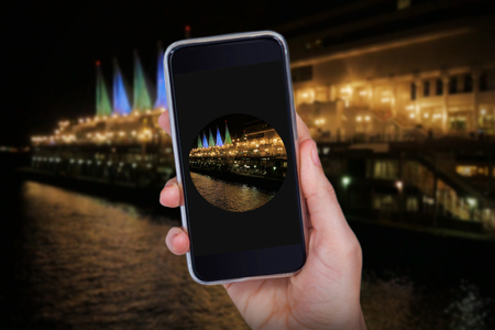 Hand holding mobile phone against white background against buildings by river in city at night