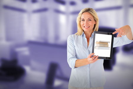 Mature student showing tablet pc against computer generated image of workplace Stock Photo