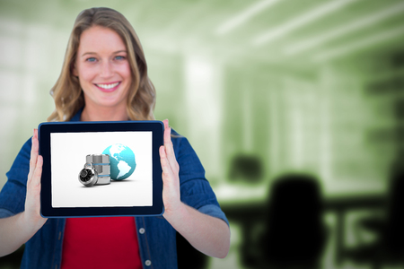 Smiling woman holding tablet pc  against digitally generated image of empty board room Stock Photo
