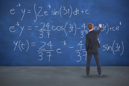 Rear view businessman writing with chalk against blue room Stock Photo
