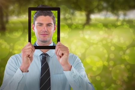 Businessman holding digital tablet in front of face against park