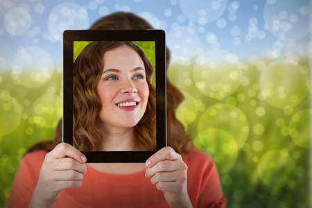 Woman holding digital tablet in front of her face against green meadow