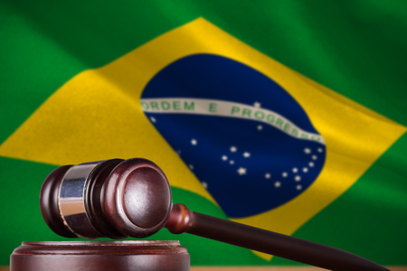 Hammer and gavel against 3d digitally generated brazil national flag