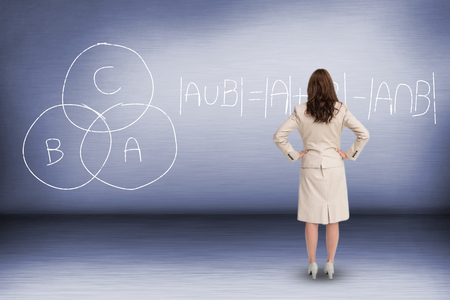 Businesswoman standing back to camera against empty room