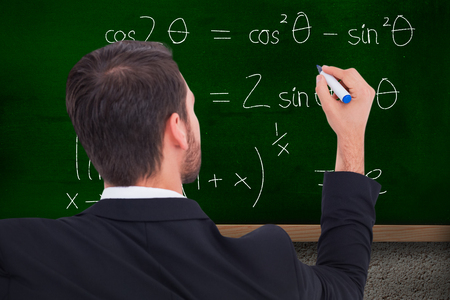 Rear view of businessman writing with marker against blackboard on wall