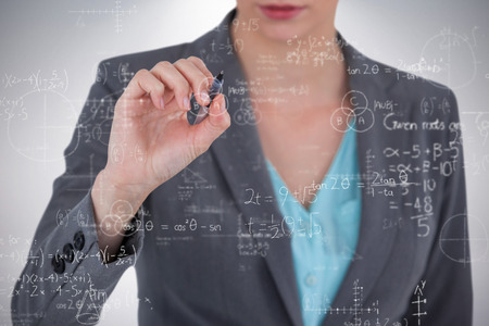 Businesswoman using invisible digital screen against grey background Stock Photo